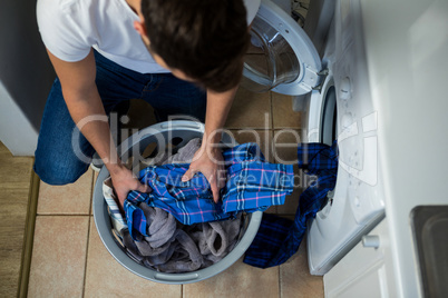 Man putting dirty clothes into washing machine