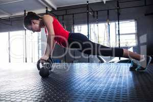 Sporty female athlete doing push-ups in gym
