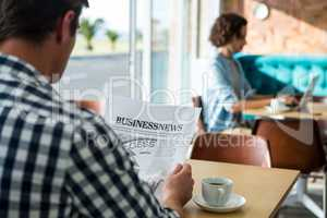 Man reading a business newspaper in coffee shop