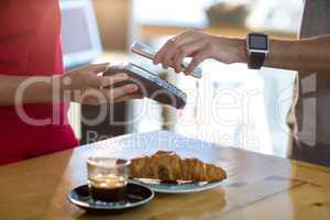 Man paying bill through smartphone using NFC technology