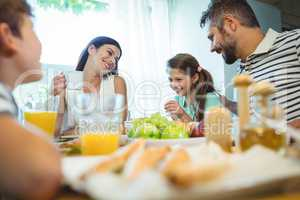 Smiling parents talking with their daughter at breakfast table