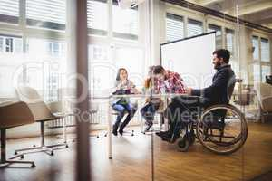 Coworker on wheelchair with photo editors in meeting room