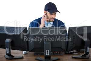 Security officer listening to earpiece while using computer