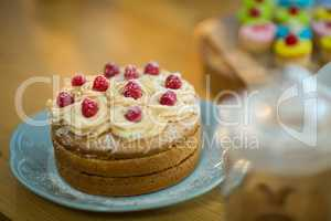 Sponge cake with whipped cream and cherry topping on plate