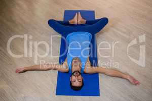 Man doing reclining bound angle pose on exercise mat
