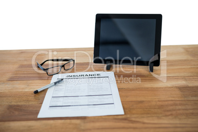 Digital tablet, insurance form, spectacle and pen on desk