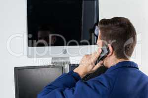 Security officer talking on telephone while looking at computer monitors