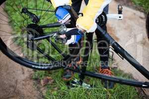 Low section of male biker repairing mountain bike