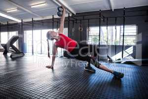 Sporty female athlete holding kettlebell in gym