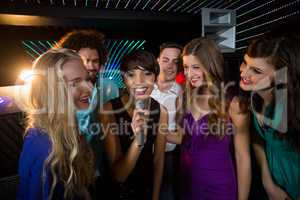 Group of friends singing song together in bar