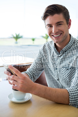 Smiling man using his mobile phone in coffee shop