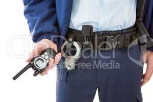 Mid section of security officer holding a walkie-talkie