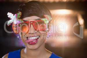 Woman wearing fancy sunglasses making funny faces in bar
