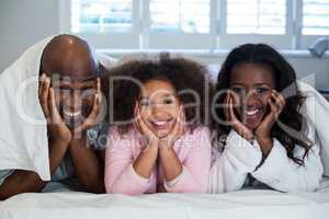Family with hands on face lying on bed