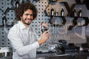 Happy waiter shaking drink in cocktail shaker in a bar