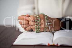 Praying hands of woman with a rosary on bible