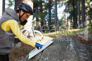 Mountain biker talking mobile phone while looking at map