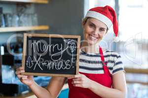 Portrait of waitress showing slate with merry x-mas sign