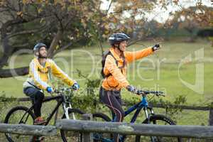 Biker couple cycling and pointing in distance