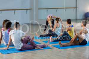 Yoga instructor helping student with a correct pose