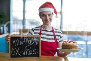 Portrait of waitress holding slate with merry x-mas sign and cake in caf�©