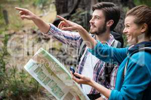 Hiker couple holding map and showing direction