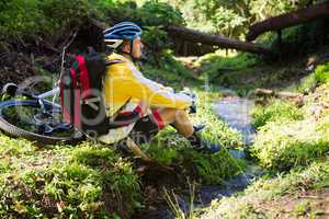 Mountain biker sitting near a stream and looking at nature