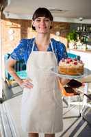 Portrait of smiling waitress holding a cake