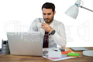 Businessman working on laptop in office while having coffee