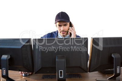Security officer talking on phone while using computer