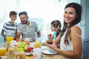 Portrait of happy woman sitting at breakfast table