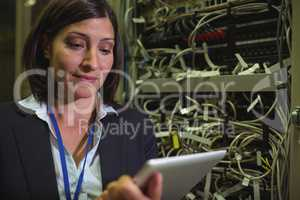 Technician using digital tablet while analyzing server