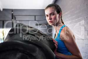 Portrait of female athlete pushing tire in gym