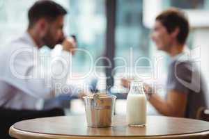 Milk bottle and bucket on table