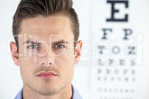 Man wearing contact lens with eye chart in background