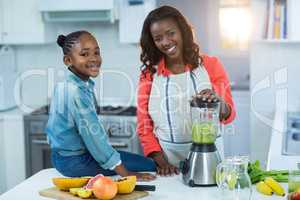 Woman and daughter using mixer