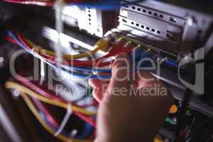 Close-Up of technician plugging patch cable in a rack mounted server