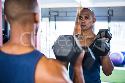 Reflection of male athlete exercising with dumbbell
