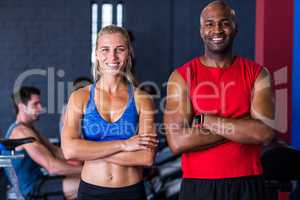Portrait of smiling friends with arms crossed in gym