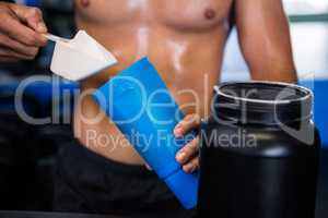 Shirtless athlete adding nutritional supplement in water