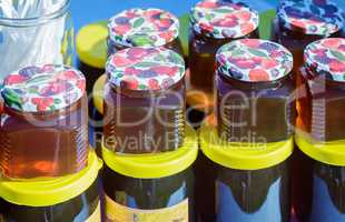 Different varieties of honey in banks, offered for sale at the f