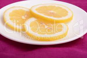 A slices of fresh yellow lemon. Lemon pieces in different sizes background