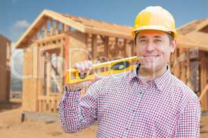 Contractor in Hardhat Holding Blueprints  and Level at Construct