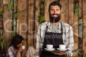 Portrait of waiter holding a cup of coffee in serving tray