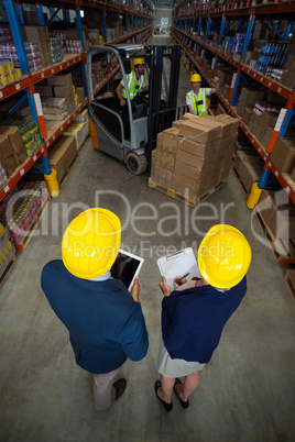 Warehouse manager and client standing