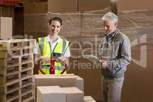 Happy warehouse manager and worker preparing a shipment