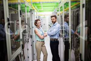 Technicians standing with arms crossed in a server room