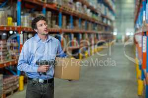 Warehouse worker holding cardboard box and barcode scanner machine