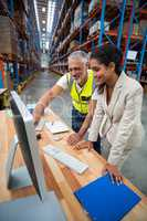 Warehouse manager and worker discussing with computer