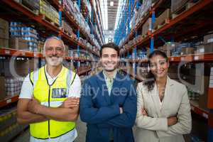 Portrait of warehouse team standing with arms crossed